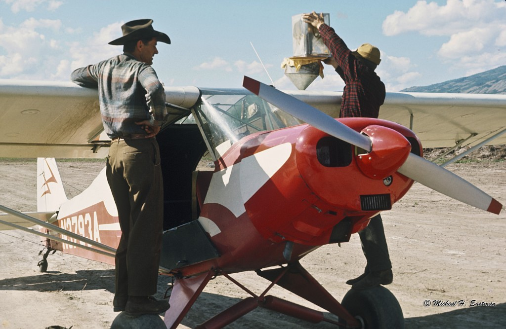 Gordon Eastman watching his friend and bush pilot, Warren Johnston, filling the Super Cub up with gas. Notice he is straining the gas.